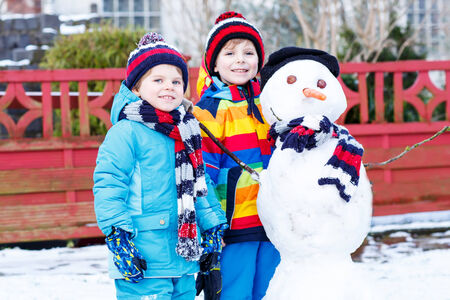 having fun in the snow: Two little siblings boys making a snowman, playing and having fun with snow, outdoors  on cold day. Active outoors leisure with children in winter. Stock Photo