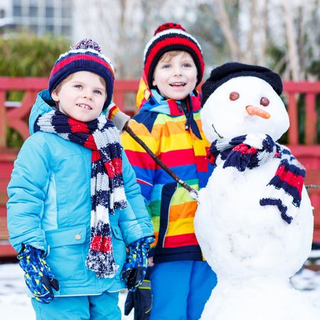 having fun in the snow: Two little friends making a snowman, playing and having fun with snow, outdoors  on cold day. Active outoors leisure with children in winter. Stock Photo