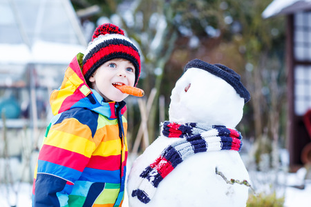 outoors: Funny little kid boy making a snowman and eating carrot, playing and having fun with snow, outdoors  on cold day. Active outoors leisure with children in winter. Stock Photo