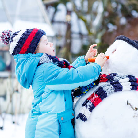 having fun in the snow: Adorable kid boy making a snowman and eating carrot, playing and having fun with snow, outdoors  on cold day. Active outoors leisure with children in winter.