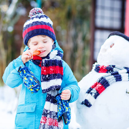 outoors: Happy little toddler boy making a snowman and eating carrot, playing and having fun with snow, outdoors  on cold day. Active outoors leisure with kids in winter.