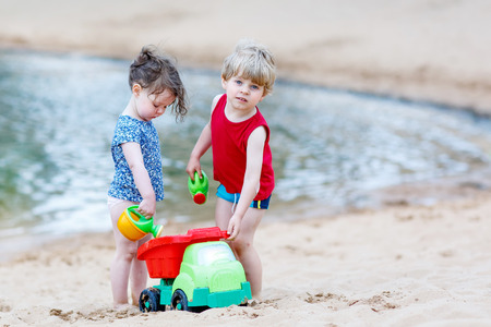 Two little friends: boy and girl having fun and playing together with sand toys near city lake on hot summer day. Active outdoors leisure with kids in summer, on sunny ay. photo