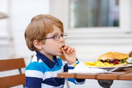 hungry kid: Cute little boy with glasses eating fast food: french fries and hamburger in cafe. Hungry kid enjoying his food, outside restaurant