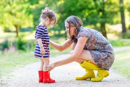 Young mother and little adorable child girl in rubber boots having fun together, family look, in summer park on sunny warm day. Stock Photo