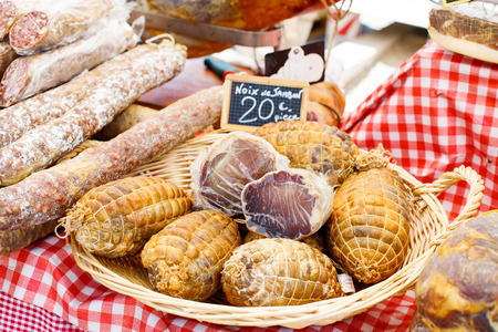 porc: French saucissons and ham display in market in south of France, Arles, Provence. Local organic food.
