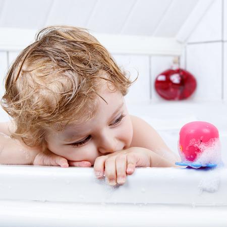 cute babies: Peque�o muchacho lindo ni�o feliz rubia divirti�ndose con agua por tomar el ba�o en la ba�era en casa. Salpicaduras chico divertido y jugando con los juguetes.