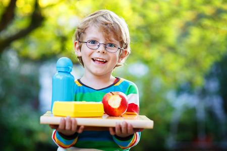 Happy little boy with books, apple and drink bottle on his first day to school or nursery. Outdoors, Back to school concept