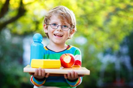 manzana agua: Ni�o peque�o feliz con los libros, la manzana y la botella de la bebida en su primer d�a a la escuela o guarder�a. Aire libre, al concepto de escuela
