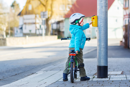 Little preschool kid boy riding with his first green bike in the city. Happy child in colorful clothes standing near traffic lights. Active leisure for kids outdoors.