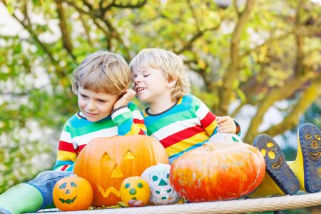 Two little kid boys making jack-o-lantern for halloween in autumn garden, outdoors. Happy children having fun together with traditional party