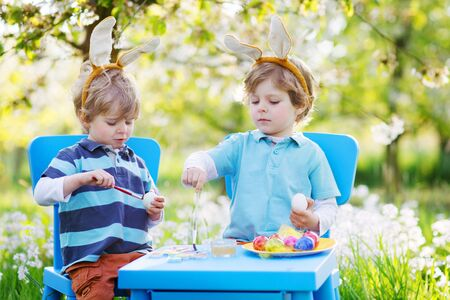 Two little sibling boys in Easter bunny ears coloring eggs in spring garden photo