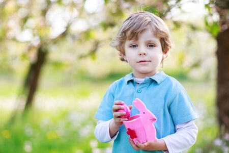 Adorable little boy celebrating Easter holiday and making egg hunt, having fun outdoors. photo