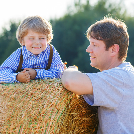 hay field: Young father and his little son having fun on yellow hay field in summer. Happy family of two. Active outdoors leisure with children on warm summer day.