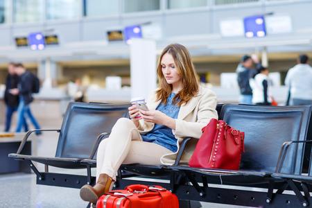 Mooi meisje bij de internationale luchthaven, het lezen van haar ebook computer en het drinken van koffie te gaan, terwijl het wachten op haar vlucht. Vrouwelijke passagier bij terminal, binnenshuis. Reizende mensen