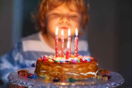 Adorable four year old kid celebrating his birthday and blowing candles on homemade baked cake, indoor. Birthday party for kids. Focus on child Standard-Bild