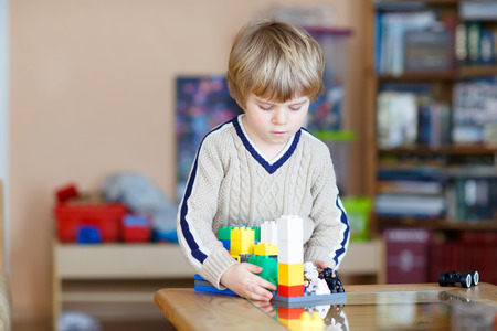 play blocks: Little blond kid boy playing with lots of colorful plastic blocks indoor. Child having fun with building and creating.