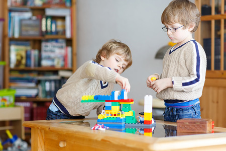 Two little kid boys playing with lots of colorful plastic blocks indoor. Children having fun with building and creating.