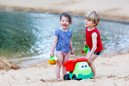 Adorable kids, two siblings, girl and boy having fun and playing together with sand toys near city lake on hot summer day. Active outdoors leisure with kids in summer, on sunny ay. photo