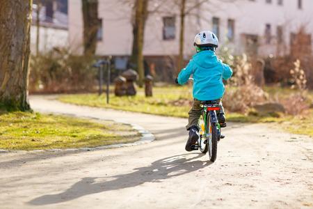 Weinig jong geitje jongen rijdt met zijn eerste groene fiets in het stadspark. Gelukkig kind in kleurrijke kleding. Actieve vrijetijdsbesteding voor kinderen buiten.
