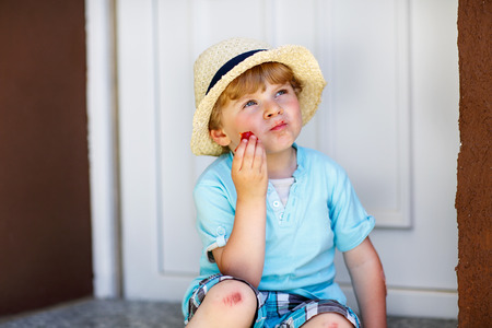 Funny little kid boy eating fresh organic strawberries in domestic garden, on warm summer sunny day. photo