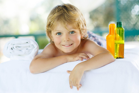Adorable little blond kid relaxing in spa with having massage. Stock Photo