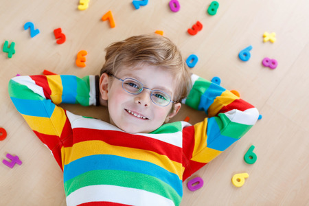 math: Little blond child with glasses playing with lots of colorful plastic digits or numbers, indoor. Kid boy wearing colorful shirt and having fun with learning math