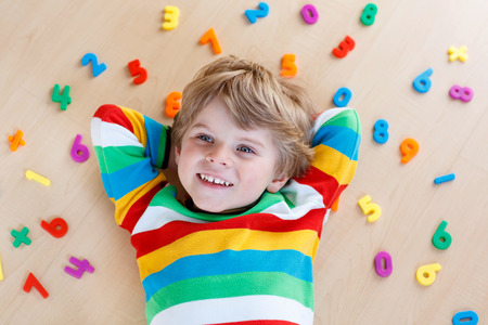 boys: Little blond toddler child playing with lots of colorful plastic digits or numbers, indoor. Kid boy wearing colorful shirt and having fun with learning math
