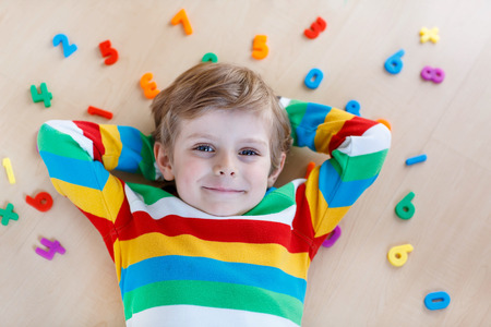 children at play: Little blond child playing with lots of colorful plastic digits or numbers, indoor. Kid boy wearing colorful shirt and having fun with learning math
