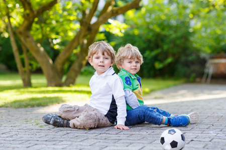 boys: Two little friends, boys playing soccer and football and having fun, outdoors. Active leisure with children on warm sunny summer day. Stock Photo