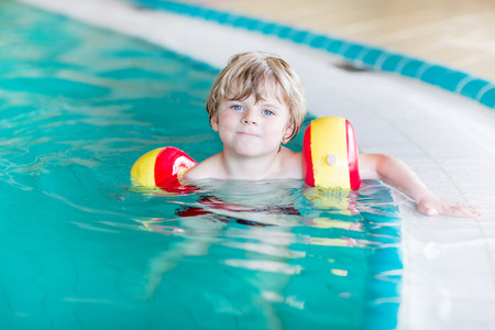 water wings: Active little toddler child, cute boy with water wings learning to swim in an indoor pool. Active and fit leisure for children.