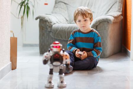 carritos de juguete: Pequeño muchacho rubio que juega con el juguete robot en casa, interior