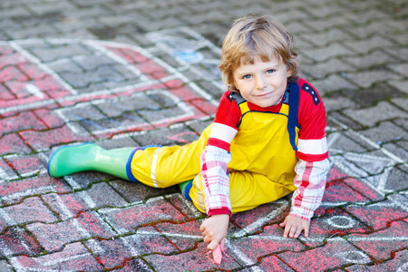 kids having fun: Creative leisure for kids: adorable child clothing as fireman having fun with fire truck picture drawing with chalk, outdoors. Dreaming of future profession.