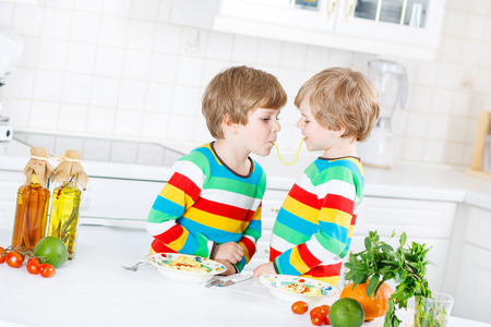 sibling: Two funny twin kids boys eating spaghetti bolognese and fresh vegetables in domestic kitchen, indoors. Sibling children in colorful shirts. Stock Photo
