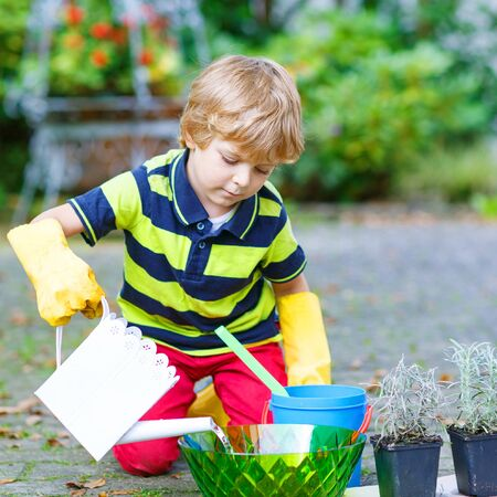 3 4 years: Little child planting flowers in homes garden or farm, on warm sunny day. Outdoors. Environment concept.