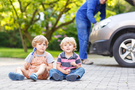 blue overall: Two little kid boys  during their father in blue overall repairing family car on background Stock Photo