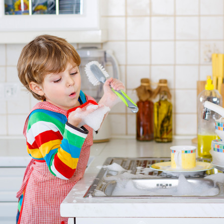 clean dishes: Adorable toddler child washing dishes in domestic kitchen. Little boy having fun with helping his parents with housework. Indoors, kid in colorful clothes.