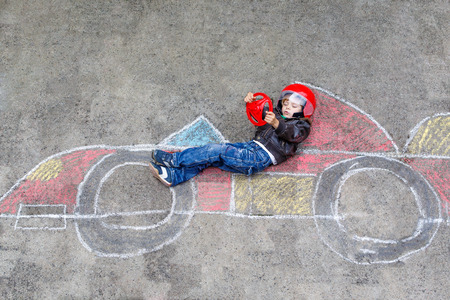 picture: Funny kid boy having fun with race car picture drawing with colorful chalks. Creative leisure for children outdoors in summer