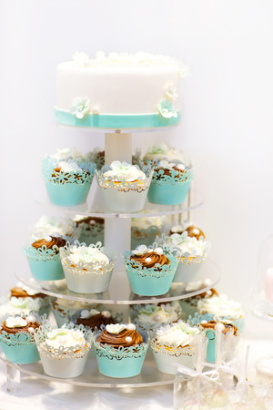 Wedding cake and cupcakes in brown and cream in blue, white and brown. Icing with cream, marzipan, details of cake.