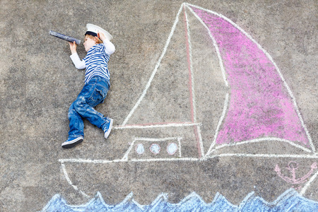 34: Cute little boy sailing on ship or boat picture drawing with chalk. Creative leisure for children outdoors in summer
