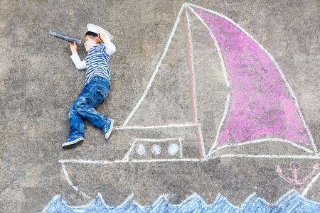 Roztomilý malý chlapec plachtění na lodi nebo lodi obrázku kreslení křídou. Creative pro volný čas pro děti venku v létě