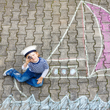 Adorable little kid boy playing with colorful chalks and painting ship or boat picture. Creative leisure for children outdoors in summer