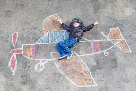 dibujo: Feliz niño pequeño niño en piloto de uniforme que se divierte con dibujo pintura avión con tiza de colores. Ocio creativo para niños al aire libre en verano.