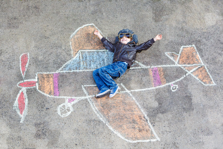 chalk drawing: Happy little kid boy in pilot uniform having fun with airplane picture drawing with colorful chalk. Creative leisure for children outdoors in summer.