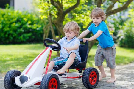ni�o empujando: Dos ni�o peque�o y de hermanos varones activos felices en divertirse con el coche de carreras de juguete en el jard�n de verano, al aire libre. Hermano adorable que empuja el coche con el ni�o m�s joven. Juegos al aire libre para los ni�os en verano concepto.