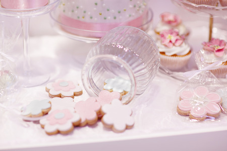 sweet table: Elegant sweet table with cupcakes and other sweets for dinner or event party. Icing with cream, marzipan, details of cake.