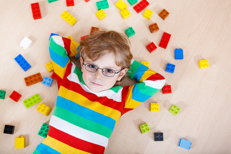 lego: Little blond kid boy playing with lots of colorful plastic blocks indoor. child wearing colorful shirt and glasses, having fun with building and creating.