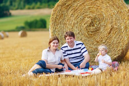 hay field: Mother, father and little son, kid boy having picnic on yellow hay field in summer, outdoors. Family having fun together.