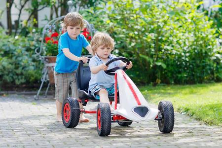 niño empujando: Dos niños pequeños niños que se divierten con carrera de coches de juguete en el jardín de verano, al aire libre. Hermano adorable que empuja el coche con el niño más joven. Juegos al aire libre para los niños en verano concepto.