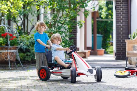 niño empujando: Dos niños de hermanos felices en divertirse con el coche de carreras de juguete en el jardín de verano, al aire libre. Hermano adorable que empuja el coche con el niño más joven. Juegos al aire libre para los niños en verano concepto. Foto de archivo