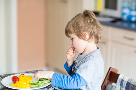 niños sanos: Happy adorable kid boy eating healthy food in kindergarten or at home. Fresh vegetables as snack for children.